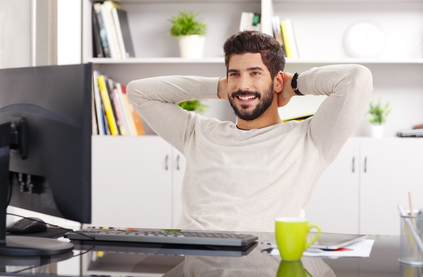 Portrait of relaxed businessman sitting at office and lening back.